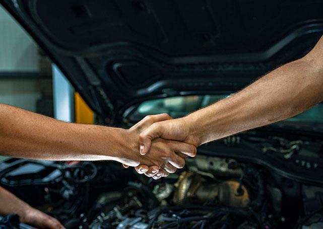 Uścisk dłoni mężczyzn przy samochodzie